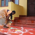 Radji dessinant un Kolam devant la Yellow House