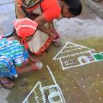 Mère et enfant dessinant un Rangoli